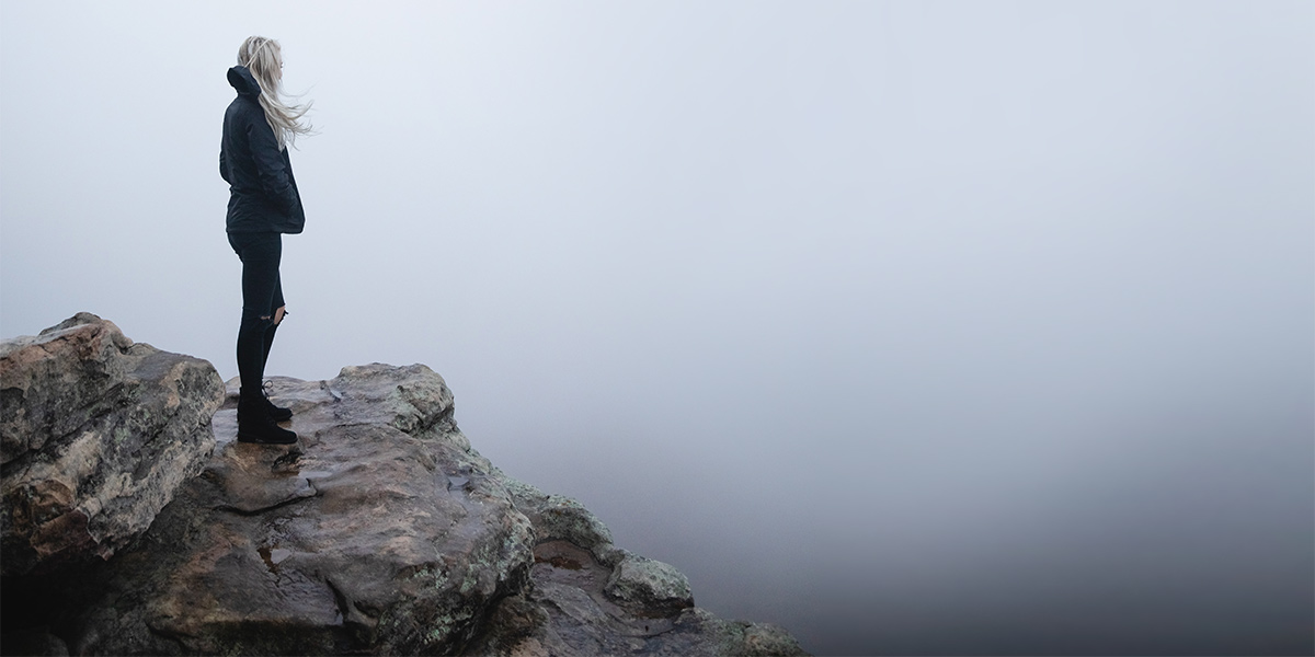 Woman standing on a high rock looking out into a misty fog - Photo by Mitchell Hartley on Unsplash