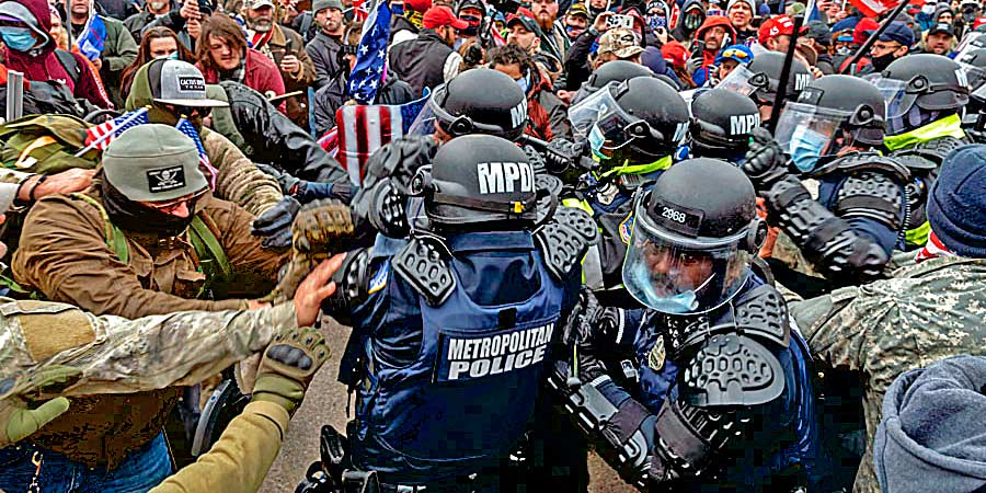 crowds rushing metropolitan police officers during the January 6, 2021 attempted coup in Washington D.C. - Credit: Flickr user Blink O'fanaye