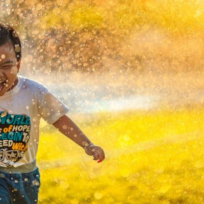 Laughing boy running through water spray in daytime - Photo by MI PHAM on Unsplash