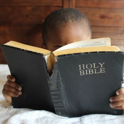 Boy reading Holy Bible while lying on bed - Photo by Samantha Sophia on Unsplash