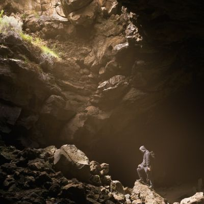 Person standing in cave with light shining on them from opening above - Photo by Ian Chen on Unsplash